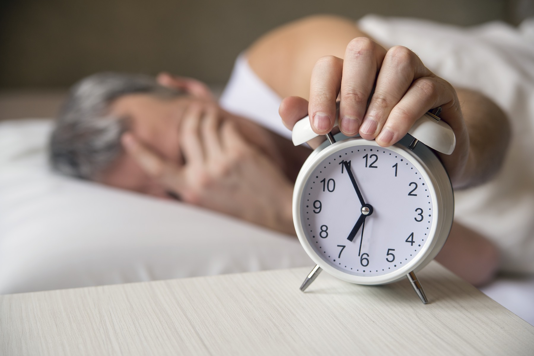 Man lying in bed turning off an alarm clock in the morning at 7am. Attractive man sleeping in his bedroom. Annoyed man being awakened by an alarm clock in his bedroom